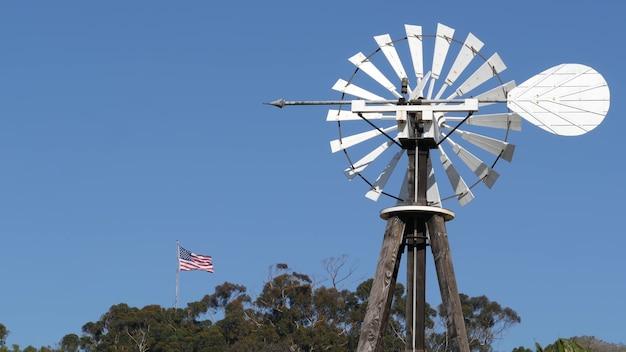 Moinho de vento, rotor laminado e bandeira dos eua contra o céu azul. turbina eólica com bomba de água, gerador de energia.