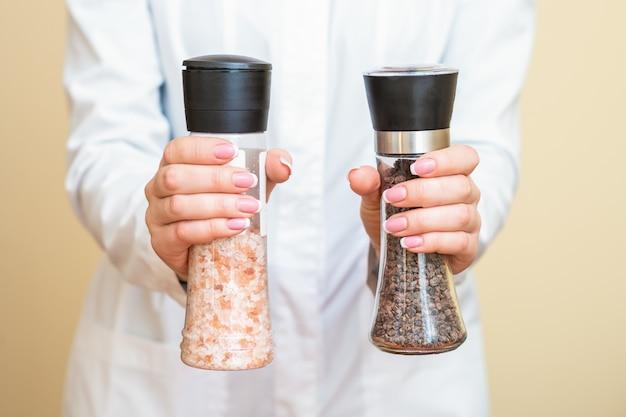Moinhos de sal e pimenta nas mãos