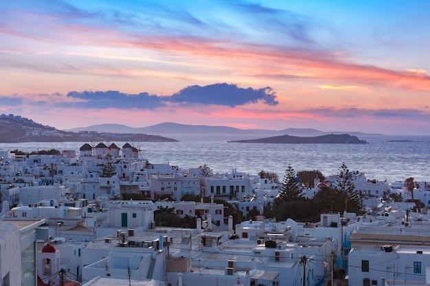 Moinhos de vento brancos tradicionais ao pôr do sol, mykonos, grécia