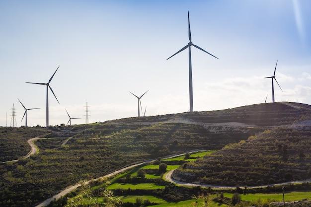 Moinhos de vento durante o dia de verão. prado verde com turbinas eólicas, gerando eletricidade.