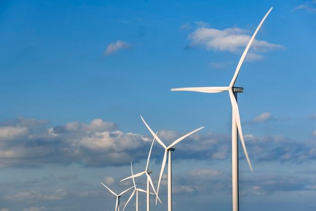 Moinhos de vento em um fundo de céu azul com nuvens. energia eólica. energia alternativa.
