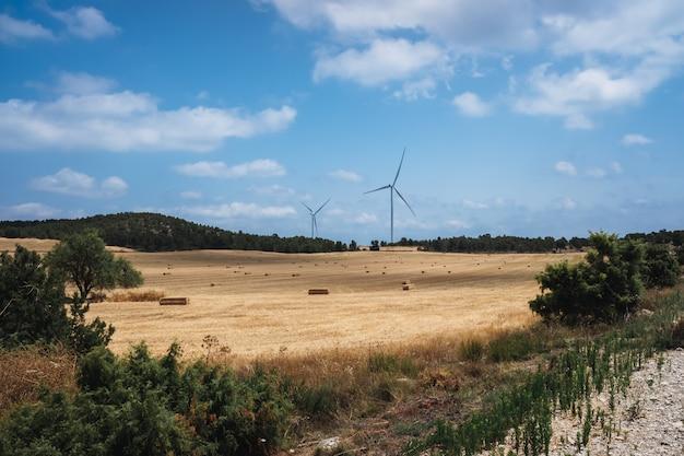 Moinhos de vento em uma área rural de cultivo de trigo no verão.