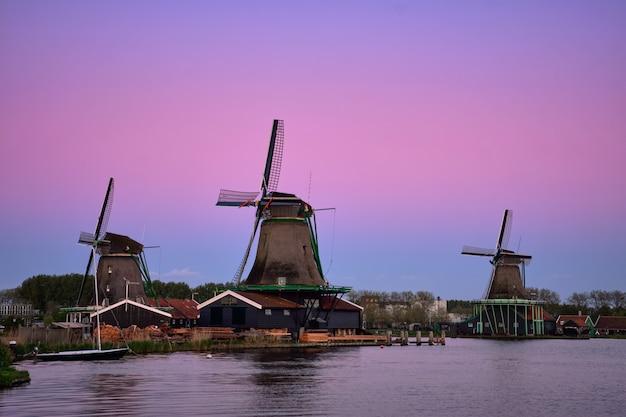 Moinhos de vento em zaanse schans na holanda no crepúsculo após o pôr do sol.