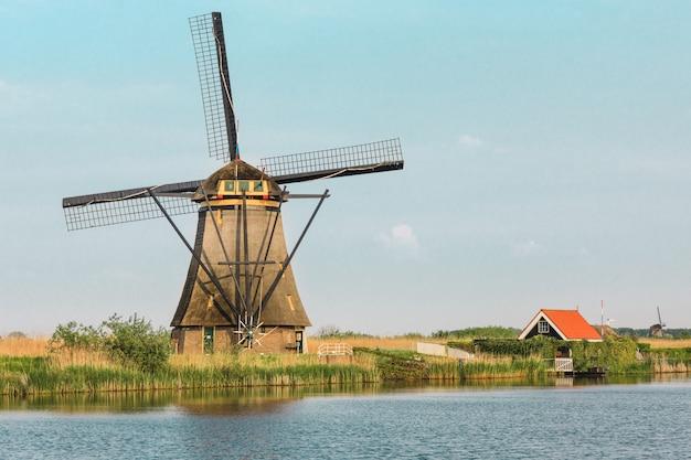 Moinhos de vento holandeses tradicionais com grama verde em primeiro plano, países baixos