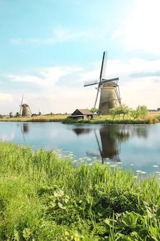 Moinhos de vento holandeses tradicionais com grama verde em primeiro plano