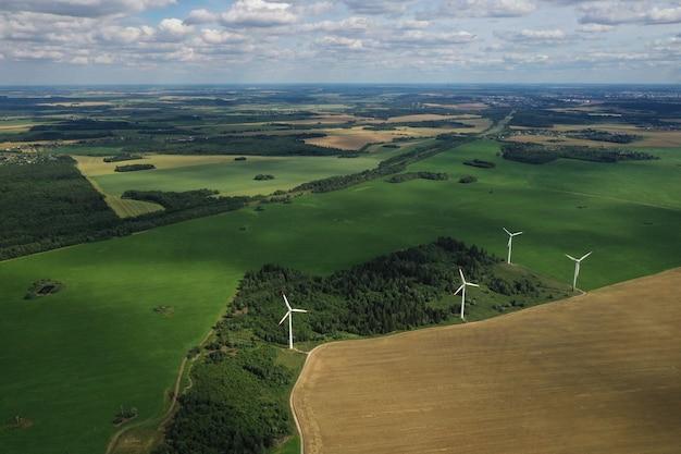 Moinhos de vento no verão em um campo verde. grandes moinhos de vento em um campo perto da floresta
