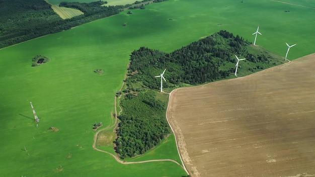 Moinhos de vento no verão em um field.large verde moinhos de vento em pé em um campo perto da floresta. europa, bielorrússia.
