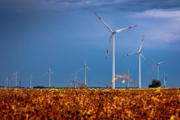 Moinhos de vento nos campos com dramáticas nuvens de chuva ao fundo