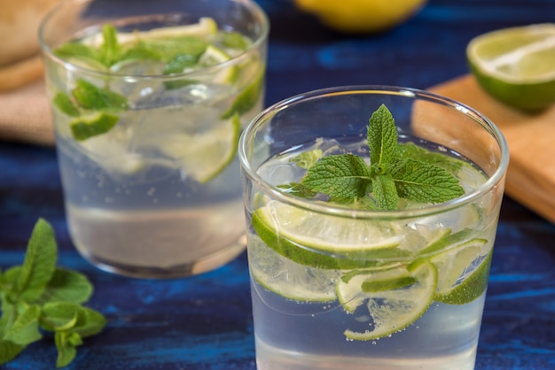 Mojito cocktail com seus ingredientes em uma mesa azul