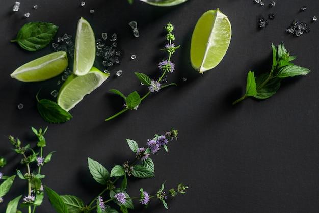 Mojito cocktail ingredientes no escuro: limão, folhas de hortelã e gelo picado