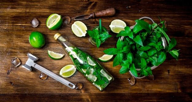 Mojito cocktail. ingredientes para cozinhar - limas, folhas de hortelã, martelo, rum na mesa de madeira. vista do topo