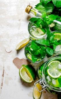 Mojito cocktail. o conceito de coquetel com limão, hortelã, rum no fundo antigo. vista do topo
