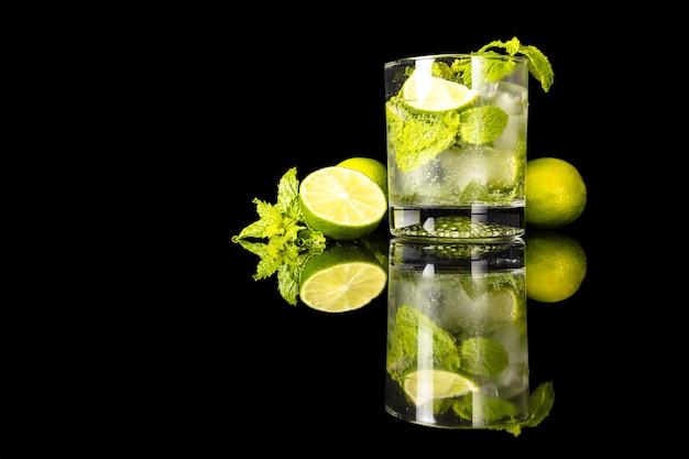 Mojito com limão e hortelã ao lado de um copo com reflexo isolado no preto