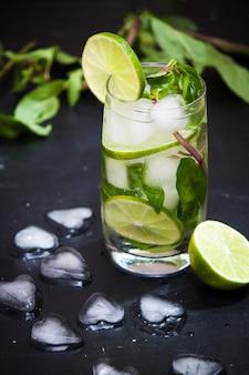 Mojito de coctail de verão com gelo, hortelã, limão em um fundo cinza. copie o espaço.