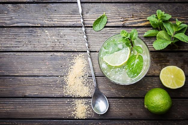Mojito de coquetel de menta refrescante com rum e limão, bebida gelada ou bebida com gelo na superfície de madeira branca, vista superior Foto Premium