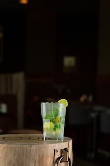 Mojito de coquetel de verão refrescante com gelo, hortelã fresca e limão. coquetel de mojito em um fundo escuro. suporte de madeira.