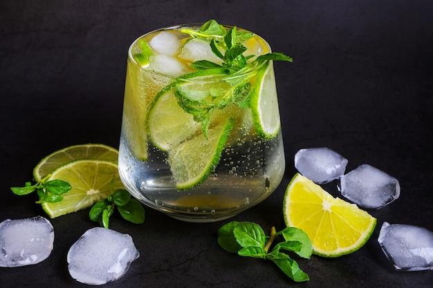 Mojito de limão em vidro transparente em fundo escuro.