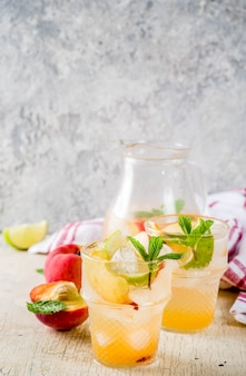 Mojito de limonada de pêssego e limão coquetel com enfeite de frutas frescas om foco seletivo de fundo concreto claro
