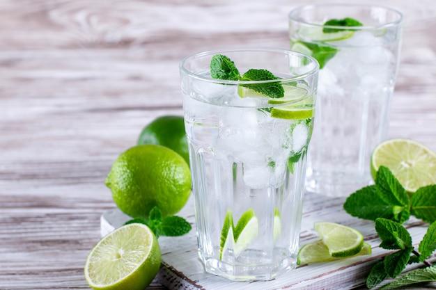 Mojito de limonada refrescante de verão em um copo com fundo branco de madeira