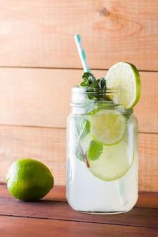 Mojito e hortelã na parede de madeira. cocktail refrescante com limão e hortelã fresca em placas de madeira. dois frascos com alças com uma bebida de verão com frutas cítricas e gelo. mojito caseiro