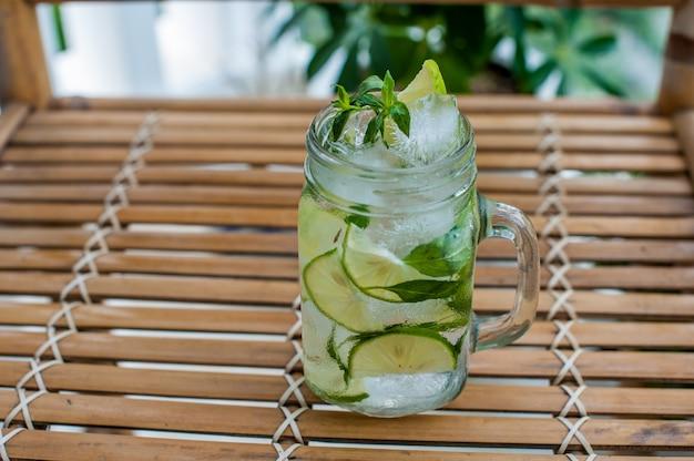 Mojito em um copo sobre uma mesa de bambu. hortelã, gelo limão