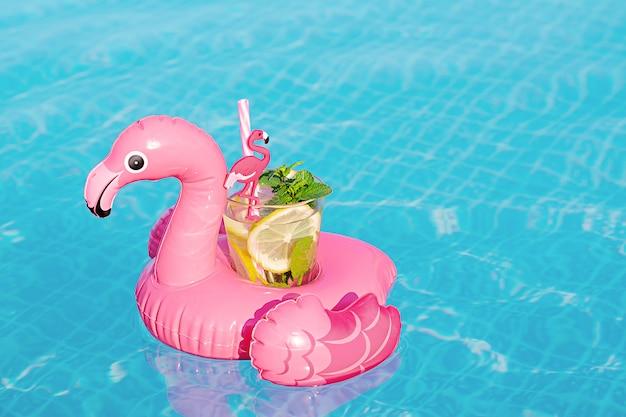 Mojito fresco do coctail no brinquedo inflável do flamingo cor-de-rosa na piscina. conceito de férias.
