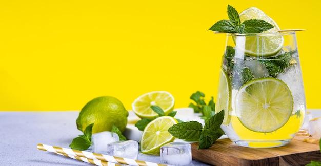 Mojito refrescante com limão e hortelã e gelo em um copo em um amarelo de verão