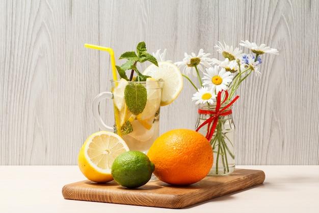 Mojito refrescante de limonada de verão com rodelas de limão e hortelã em um copo alto e limonada de morango com hortelã em um copo baixo em uma tábua de madeira