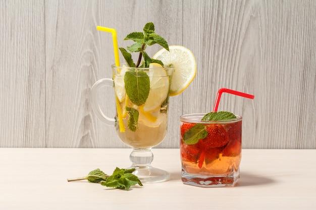 Mojito refrescante de limonada de verão com rodelas de limão e hortelã em um copo alto e limonada de morango com hortelã em um copo baixo