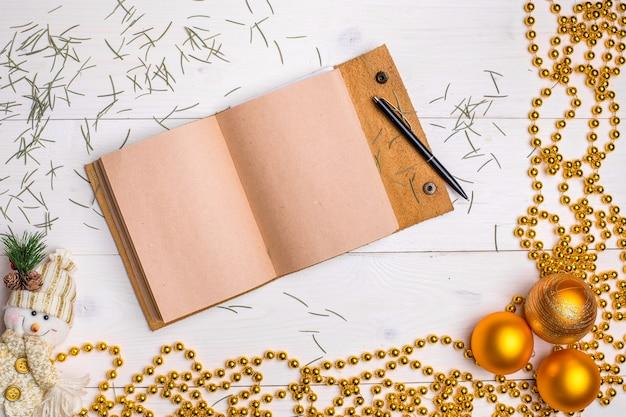 Mokcup de ano novo e natal. caderno com luzes de natal em fundo branco de madeira, espaço para seu texto, copyspace flat lay style.