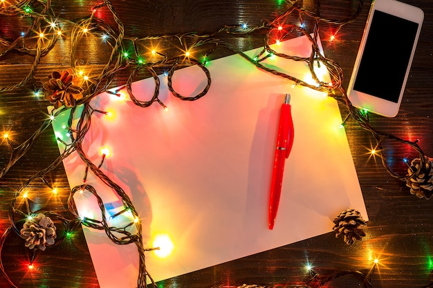 Mokcup de ano novo e natal. caderno com luzes de natal em fundo de madeira, espaço para seu texto, copyspace. de cima. conceito de planejamento de férias de inverno. estilo liso leigo.