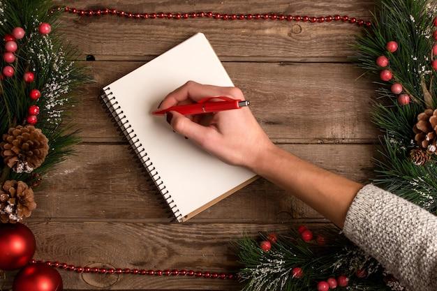 Mokcup de ano novo e natal. mão escrevendo em um caderno com luzes de natal em fundo de madeira, espaço para seu texto, copyspace. de cima. conceito de planejamento de férias de inverno. estilo liso leigo.