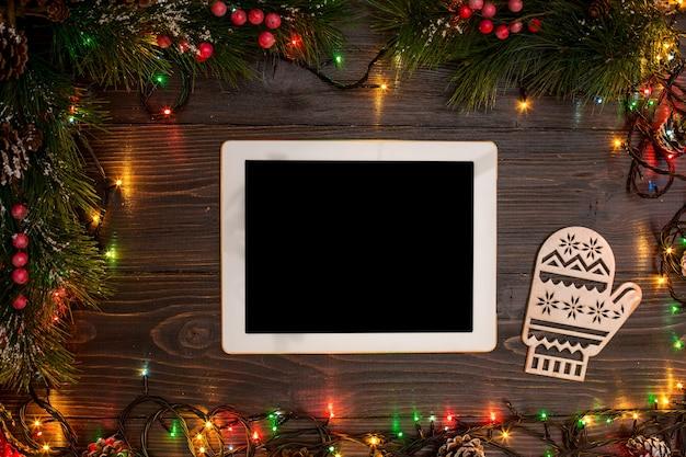 Mokcup de ano novo e natal. tablet, smartphone com luzes de natal em fundo de madeira, espaço para seu texto, copyspace. de cima. conceito de planejamento de férias de inverno. estilo liso leigo.