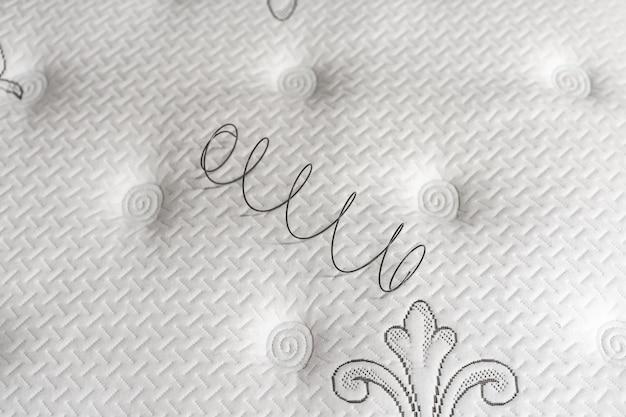 Mola de metal em colchão branco