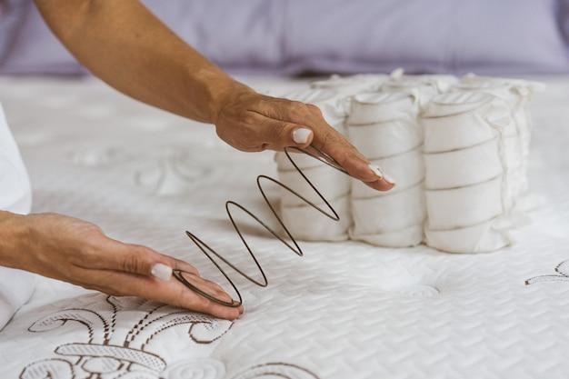 Mola do colchão nas mãos de uma mulher