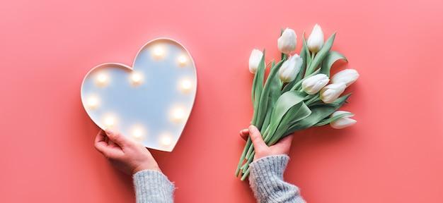 Mola geométrica plana lay com coração forma lightboard e flores tulipa branca em fundo rosa
