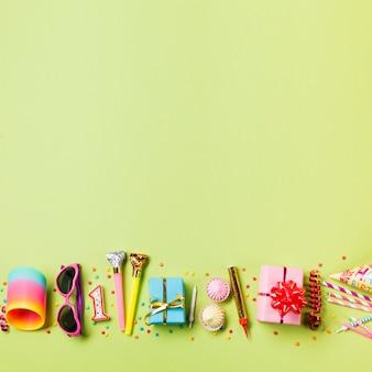 Molas coloridas; oculos escuros; vela; chifre de festa; caixa de presente; aalaw; serpentina e bebendo palhas no pano de fundo verde
