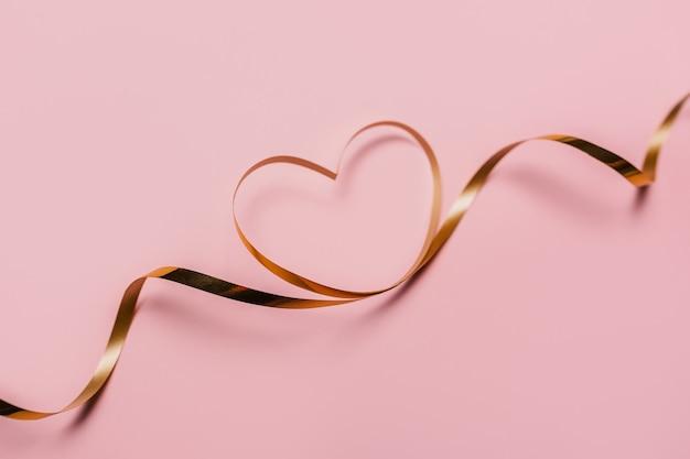 Moldar o coração com uma fita dourada em fundo rosa isolado