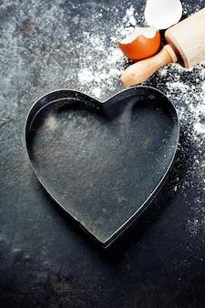 Molde de cozimento em forma de coração com rolo e farinha