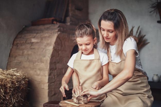 Molde de mãe e filha com argila, apreciando a arte da cerâmica e o processo de produção