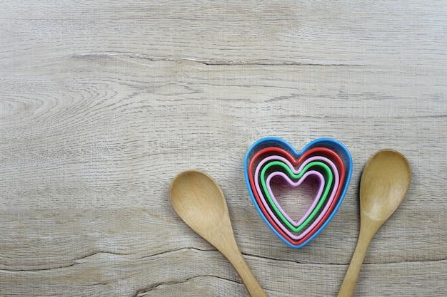 Molde em forma de coração e colher de pau repousa sobre uma mesa de madeira e tem um espaço de cópia para design no amor e dia dos namorados.