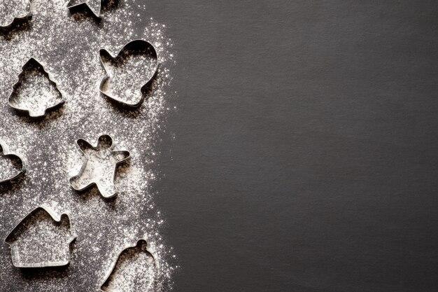Moldes de biscoitos de natal e farinha em fundo preto
