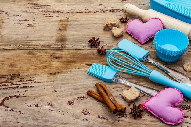 Moldes de silicone para cupcakes, especiarias, açúcar, bata, espátula, rolo e corações de feltro. tábuas de madeira velhas