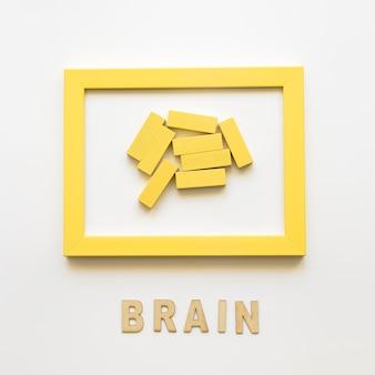 Moldura amarela com blocos de madeira perto da palavra cérebro