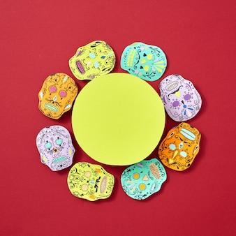 Moldura amarela redonda decorada com papel assustador enfrenta atributos de calaveras do feriado mexicano calaca em um fundo vermelho com espaço para texto. cartão de artesanato de halloween. postura plana
