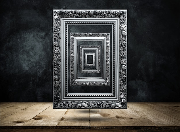 Moldura antiga prata na parede escura do grunge com tampo da mesa de madeira misteriosa, confuso, fundo