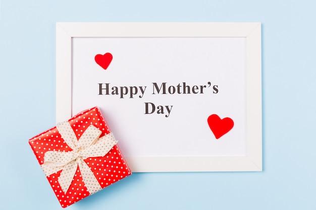 Moldura branca com texto feliz dia das mães, caixa de presente e coração vermelho sobre fundo azul claro. feliz dia das mães conceito.