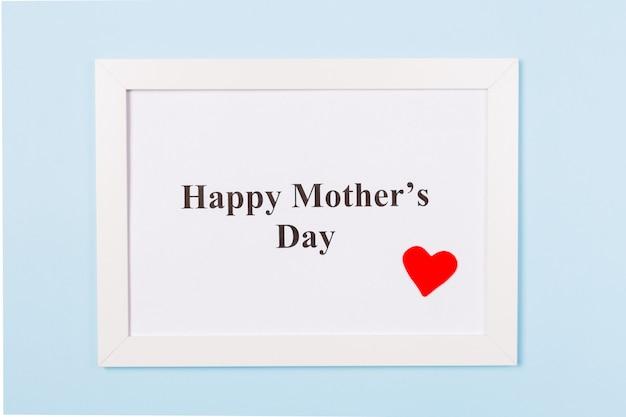 Moldura branca com texto feliz dia das mães e coração vermelho sobre fundo azul claro. feliz dia das mães conceito.