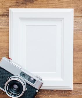 Moldura branca em fundo de madeira com câmera antiga