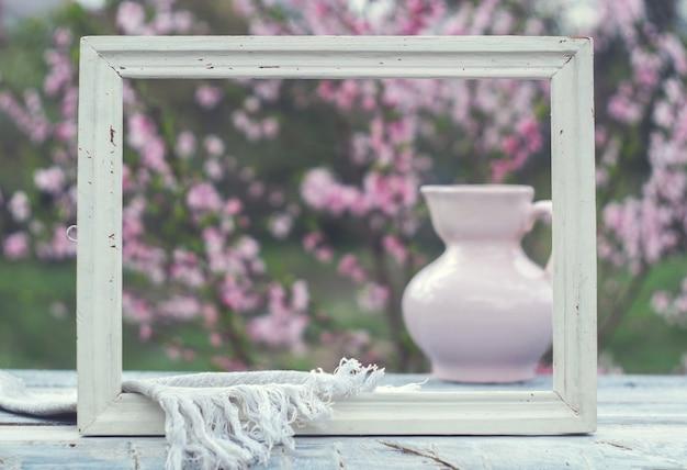 Moldura branca, jarro de porcelana rosa e guardanapo em uma mesa de quadros brancos contra o fundo de um arbusto florido